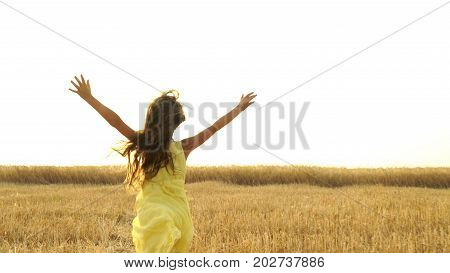 young girl in the dress is running across the field. Freedom concept