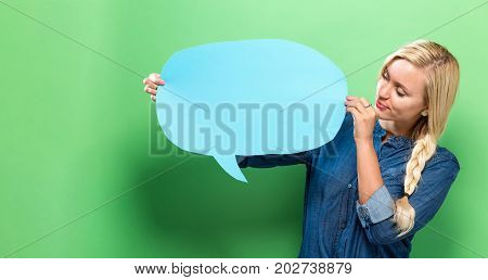 Young woman holding a speech bubble on a solid background