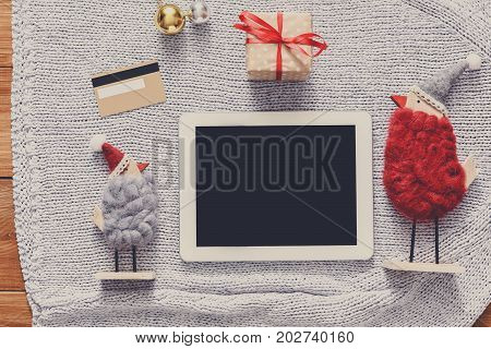 Christmas online shopping background. Tablet screen with copy space top view on warm knitted sweater cloth, present box and credit card. Electronic device, internet sales on winter holidays concept