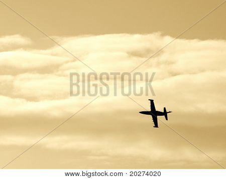 Silhouette of the fighter aircraft in the air. Sepia toned