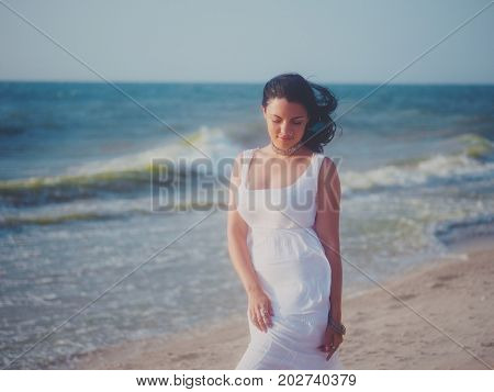 The young girl enjoys good windy weather on sea beach. Woman is dressed in white sundress and boho jewelry rest at the sea. Carefree and freedom concept. Portrait of gypsy lady.