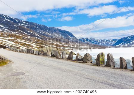 Old road with stones in summer with snow in Norway mountains