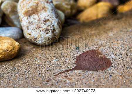 A horizontal closeup photo of a heart shape stained on cement with stones in soft focus in the background