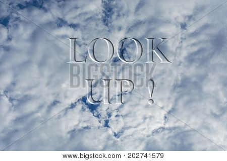 The sky with white clouds with the inscription Look up. Bottom view.
