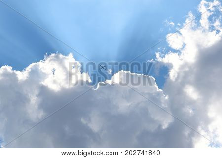 Clouds and blue sky with an airplane emerging from the clouds with sun streaks.