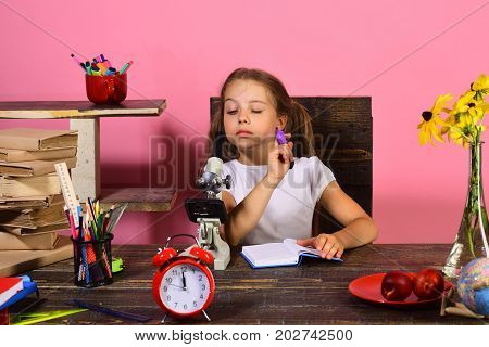 Schoolgirl with interested face writes in copybook and looks into microscope. Back to school and childhood concept. Kid and school supplies on pink background. Girl sits at desk with books and clock