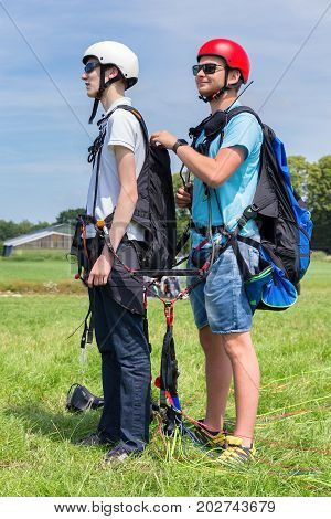 Paragliding instructor with boy preparing for tandem flight