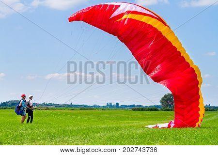 Paragliding instructor with boy preparing mattress flyer