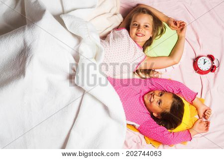 Children With Smiling Faces Lie On Pink And White Background