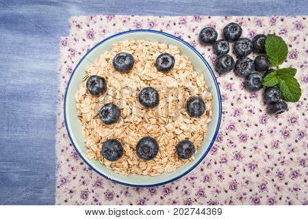 Oat flakes with blueberries in a bowl on cute fabric background. Top view with copy space.