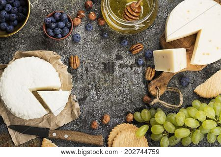 Young white cheese, a new recipe for cheese with fenugreek, a hard chopped Parmesan on a gray stone background with blueberries, nuts, green grapes, honey. Top view. Selective focus.