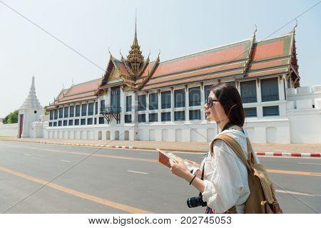 Sweet Female Backpacker Holding Travel Guidebook