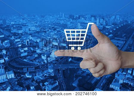 Shopping cart icon on finger over modern city tower street and expressway Shop online concept