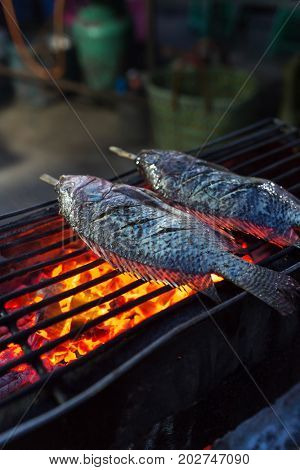 Grilled fish with salt crust and herb on grill