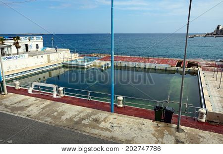 BUGIBBA, MALTA - MARCH 29, 2017 - Old unused swimming pool along the waterfront Bugibba Malta Europe, March 29, 2017.