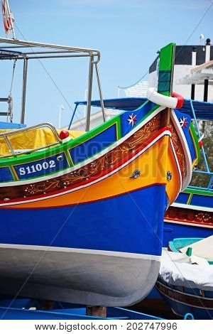 BUGIBBA, MALTA - MARCH 29, 2017 - The bow of a brightly painted traditional Dghajsa boat in a boatyard Bugibba Malta Europe, March 29, 2017.