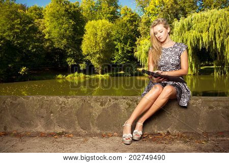 Technology outdoor relaxation concept. Woman sitting in park relaxing and using tablet ebook spending her leisure time outside