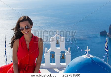 Santorini travel tourist brunette woman in red dress visiting famous white Fira city. Greece, Europe.