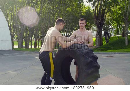 Two young men rolling a wheel in order to do exercises