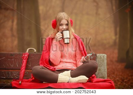 Autumn season time people concept. Young woman holding thermal mug. Cold weather outside. Lady has red clothing listening music