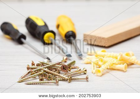 Screwdrivers, Wooden Block And Screws On White Wooden Background