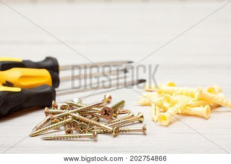 Screwdrivers and screws with plastic dowels on white wooden background. Shallow depth of field