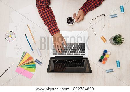 Male fashion desginer working at desk with fashion sktech. Top view.