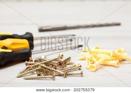 Screwdrivers drill and screws with plastic dowels on white wooden background. Shallow depth of field