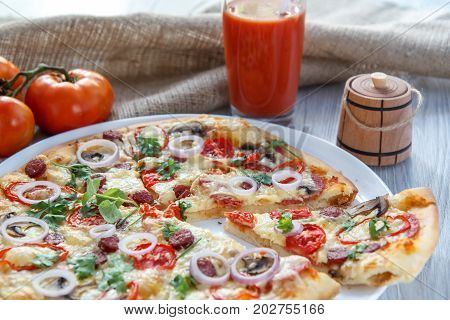 Sliced Whole Fresh Pizza With Tomatoes, Salami, Cheese And Mushrooms On White Plate
