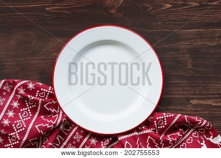 Christmas dinner background plate and napkin on dark rustic wooden table top view