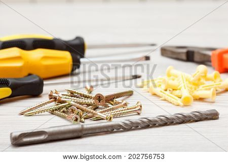 Screwdrivers, Drill, Pliers And Screws On White Wooden Background