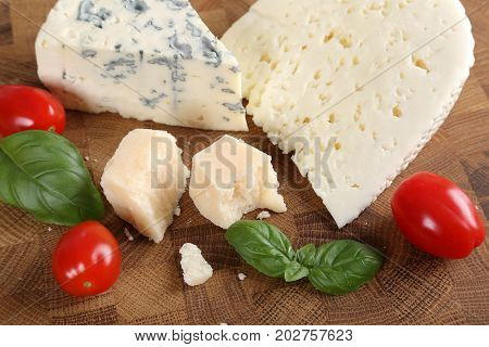 Delicacy. Food composition - different types of cheeses and tomatoes.
