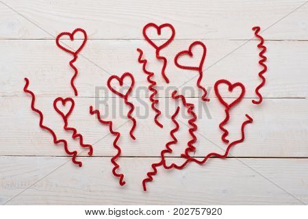 Red Fuzzy Wire Hearts And Ringlets On White Vintage Background
