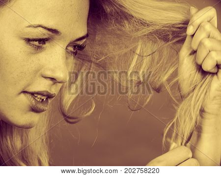 Haircare health problem concept. Unhappy sad woman looking at damaged split ends on her blonde hair. Sepia
