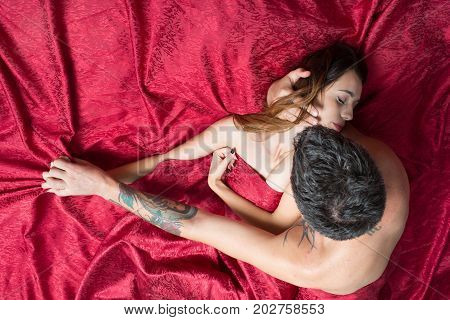 Man With Tattoos Holds Pretty Sleeping Lady In Arms