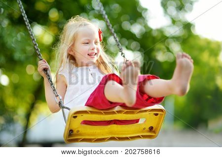 Cute Little Girl Having Fun On A Playground Outdoors On Warm Summer Day