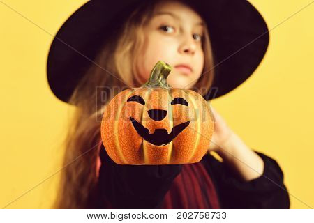 Kid In Black Witch Hat And Dress. Girl With Pumpkin