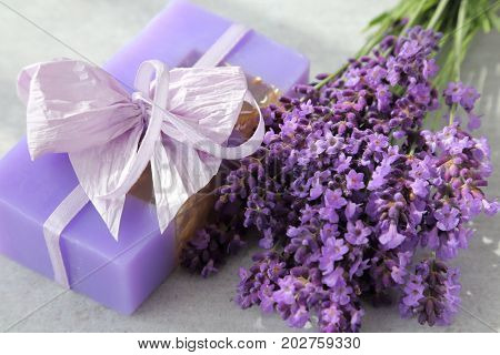 Bouquet of lavender and lavender soap on a gray background.