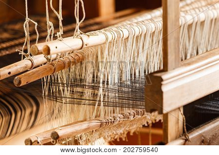 Traditional devices vintage tailoring equipment concept. Oldfashioned thread on old spindle spinning wheel