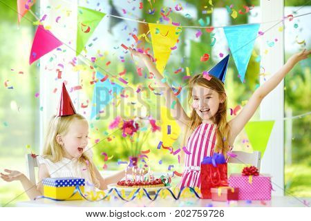 Two Funny Little Sisters Having Birthday Party At Home, Blowing Candles On Birthday Cake