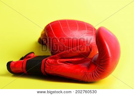 Red boxing gloves on juicy yellow background close up. Concept of sportive lifestyle and knock out