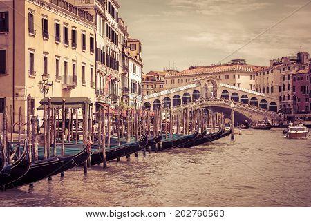 Touristic gondolas are on the Grand Canal near the Rialto Bridge in Venice, Italy. Rialto Bridge is one of the main tourist attractions in Venice.