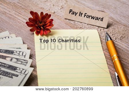 Top 10 Charities concept on notebook and wooden board