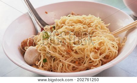 To clenching the egg noodle at food shop and photo extra close up see detail Have fish and pork ball parsley green onions sliced shrimp dumplings in white plastic bowls.