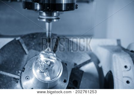 The 5-axis CNC milling machine cutting the automotive part with the cutting ballnose tool.Hi-technology machining concept.