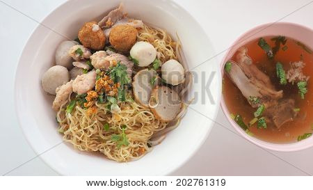 Egg noodle dry Asian food with bone soup top view and close up see detail Have fish and pork ball parsley green onions sliced bone soup shrimp dumplings in white plastic bowls isolate on white background.