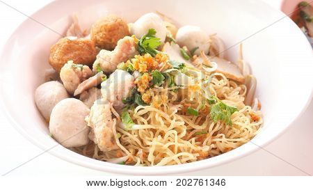 Egg noodle dry Asian food close up see detail and macro photo Have fish and pork ball parsley green onions sliced shrimp dumplings in white plastic bowls.