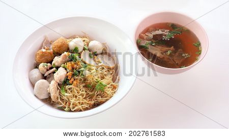 Egg noodle dry Asian food Have fish and pork ball parsley green onions sliced bone soup shrimp dumplings in white plastic bowls isolate on white background has copy space and clipping paths.