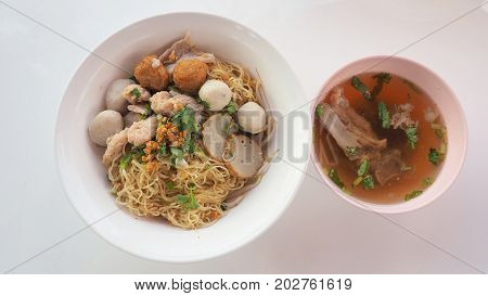 Egg noodle dry Asian food with bone soup top view Have fish and pork ball parsley green onions sliced bone soup shrimp dumplings in white plastic bowls isolate on white background.