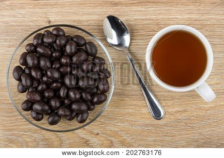 Dragee Peanuts In Cacao Powder, Tea And Teaspoon On Table
